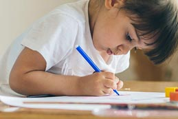 child drawing on notepad