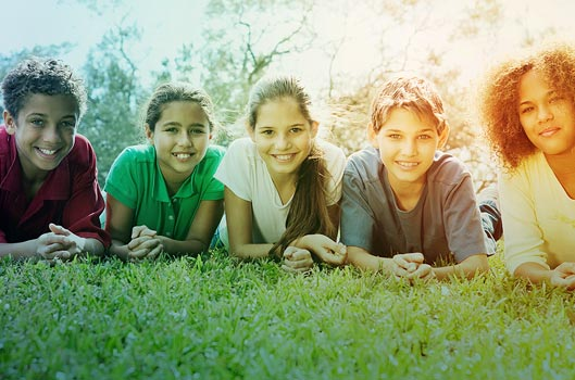 Kids lying in grassy field